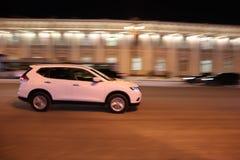 Branco o carro atravessa rapidamente a cidade da noite fotos de stock royalty free