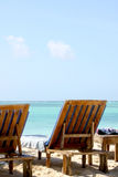 Branco Sandy Beach And Wooden Chairs de Zanzibar Foto de Stock Royalty Free