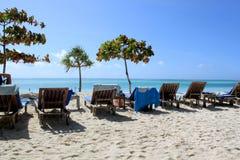 Branco Sandy Beach And Wooden Chairs de Zanzibar Fotografia de Stock