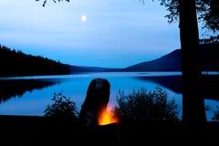 Brand över sjön under fullmånen fotografering för bildbyråer