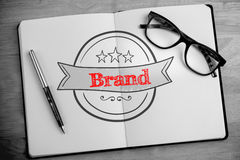 Brand against overhead of open notebook with pen and glasses Royalty Free Stock Photo