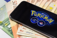Brand black Apple iPhone 6s and Pokemon on the screen. With money. Pokemon Go, a free-to-play augmented reality mobile game developed by Niantic for iOS and stock photos