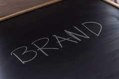 Brand on the Blackboard. Handwritten chalk text BRAND on the blackboard Stock Image