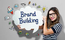 Brand Building text with woman holding a speech bubble. Brand Building text with young woman holding a speech bubble stock images