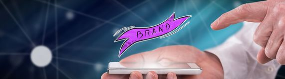 Concept of brand. Brand concept above a smartphone held by a man royalty free stock photography