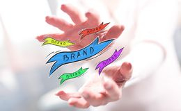 Concept of brand. Brand concept between hands of a woman in background royalty free stock photography
