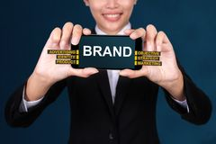 BRAND concept, Happy businesswoman Show text brand on Smart Phone royalty free stock images