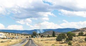 Brand in de afstand in Noordelijk Californië die - op 2 steegweg dichtbij Susansville met bergen drijven en rook in de afstand -  Stock Foto