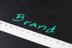Brand engagement KPI with measurable metrics in online and offline marketing campaign concept, measuring tape with centimeter wit. H handwriting chalk word Brand stock photo