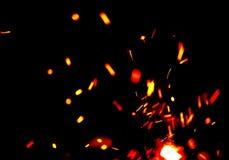 Brand flammar med gnistor över svart Arkivfoto