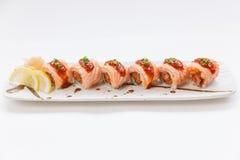 In Brand gesetzter Salmon Maki Roll mit rohem Salmon Inside Topping mit Soße und weißem indischem Sesam Gedient mit Scheiben-Zitr lizenzfreie stockfotografie