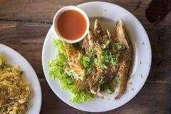 In brand gestoken vissen met knoflook en verse groente op schotel Stock Afbeeldingen