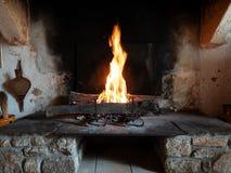 Brand i en öppen forntida spis i ett träantikt stenhus arkivbild