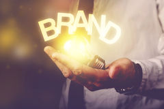 Brand idea. Concept with businessman holding light bulb, retro toned image, selective focus royalty free stock photo