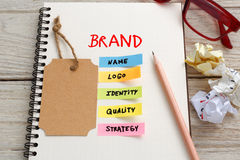 Brand marketing concept with brand tag on notebook. Brand marketing concept with notebook, brand tag and coffee cup on work desk stock photos