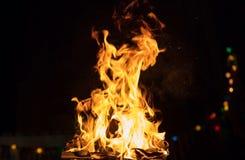 Brand met vlammen en bokeh lichten Grote uitbarsting op zwarte vage achtergrond Sluit omhoog mening met details, ruimte voor teks stock afbeeldingen