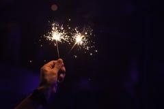 Brand mit zwei Wunderkerzen in einer männlichen Hand Lizenzfreie Stockfotos