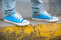 Brand new blue shoes and yellow concrete edge. Urban walking theme. Closeup photo with selective focus and shallow DOF Stock Images