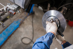 Brand new brake disc on car in a garage. Auto mechanic repairing . Royalty Free Stock Images