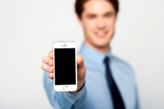 Brand new cellphone is out for sale, buy now!. Young sales guy displaying brand new cellphone Royalty Free Stock Photography