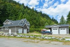Brand new family house with car and boat parked on gravel driveway. New residential house and detached double garage on country side in British Columbia stock photo