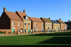 Brand new houses on a village green. New housing estate in Swindon, Wiltshire, UK. Rather than having houses built in the same style, modern luxury estates Stock Photography