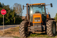 Brand new orange tractor at the end of the village Stock Photo