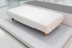 Brand new sofa bed with white cover fitted sheet and wooden leg Stock Photo