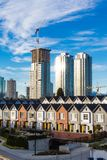 Brand new townhouses in a row on bright sunny day with Highrises in the background. Blue sky royalty free stock photography