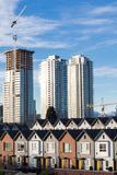Brand new townhouses in a row on bright sunny day with Highrises in the background. New townhomes and highrise development.Is the solution for housing crisis royalty free stock images