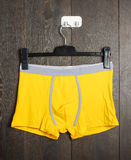 Brand new vivid yellow slips on the hanger Royalty Free Stock Photography