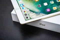 Brand new white Apple iPad Gold. Kyiv, Ukraine - Fabruary 6, 2018: Brand new white Apple iPad Gold with box on black wooden background closeup, 7th generation of Royalty Free Stock Photo