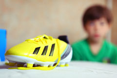 Brand new yellow football boots close up. Photo with boy on background Royalty Free Stock Photo