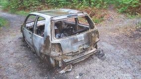 Brand och rostig bil som längs vägen överges i skog Royaltyfri Foto
