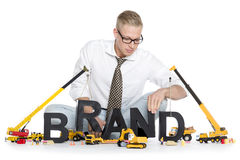 Brand start up: Businessman building brand-word. Stock Photography