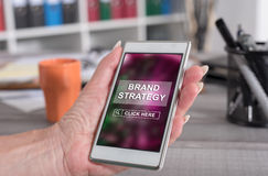 Brand strategy concept on a smartphone. Female hand holding a smartphone with brand strategy concept royalty free stock photography