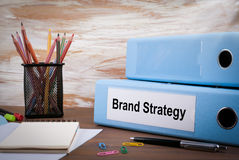 Brand Strategy, Office Binder on Wooden Desk. On the table colored pencils, pen, notebook paper Stock Photo