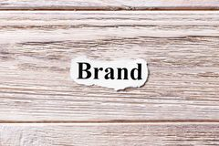 BRAND of the word on paper. concept. Words of BRAND on a wooden background royalty free stock photography