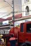 Brandambtenaar naast brandvrachtwagen tijdens huisbrand die binnenlandse barakhuizen uithaalde royalty-vrije stock afbeelding
