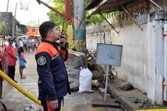 Brandambtenaar naast de holdingsradio van de brandvrachtwagen tijdens huisbrand die binnenlandse barakhuizen uithaalde stock afbeelding