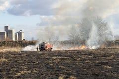 Brandbekämpning på fältet runt om den industriella zonen Royaltyfri Bild