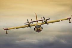 Brandbekämpningflygplan som flyger lågt under utställning arkivbild
