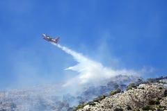 Brandbekämpningnivån släcker en brand på backen Grekland Arkivbild