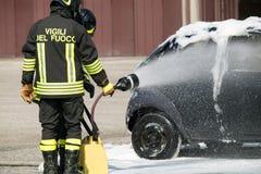 Brandbestrijder in actie met schuim om de brand te doven Stock Foto