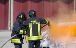 Brandbestrijder in actie met schuim om de brand te doven Stock Fotografie