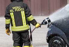 Brandbestrijder in actie met schuim om de brand te doven Royalty-vrije Stock Afbeelding