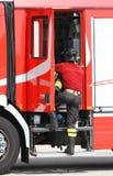 Brandbestrijder dichtbij de brandvrachtwagen wanneer het behandeling van een noodsituatie Stock Foto's