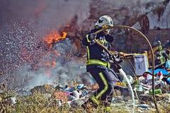 Brandbestrijder die brand dooft Stock Fotografie