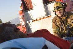 Brandbestrijder Looking At Patient stock afbeelding