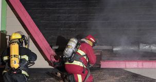 Brandbestrijder op dak met aanvalspijp stock video